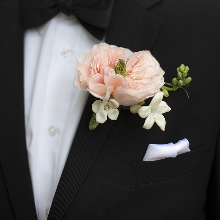 Charity rose in button hole groom