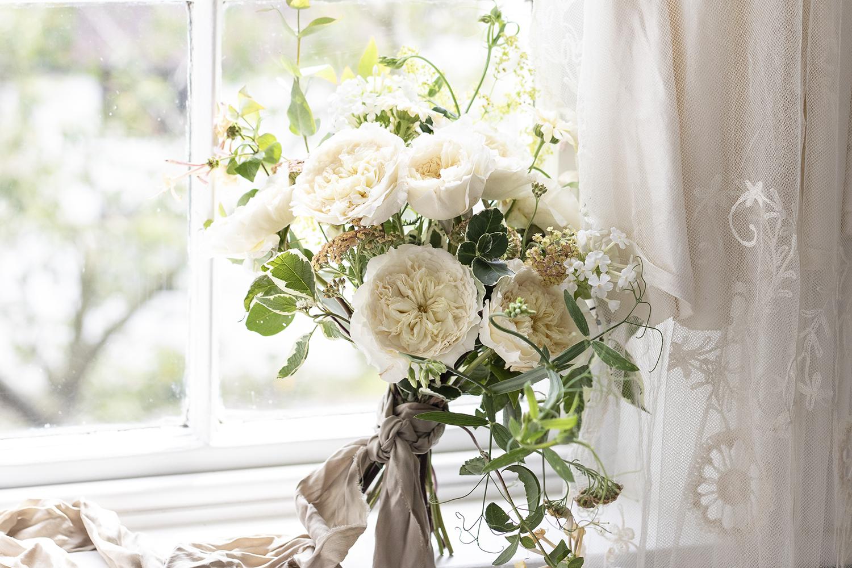 Patience cream roses wedding bouquet on windowsill
