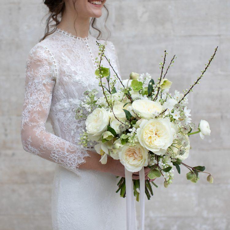 Bride holding bouquet white roses David Austin